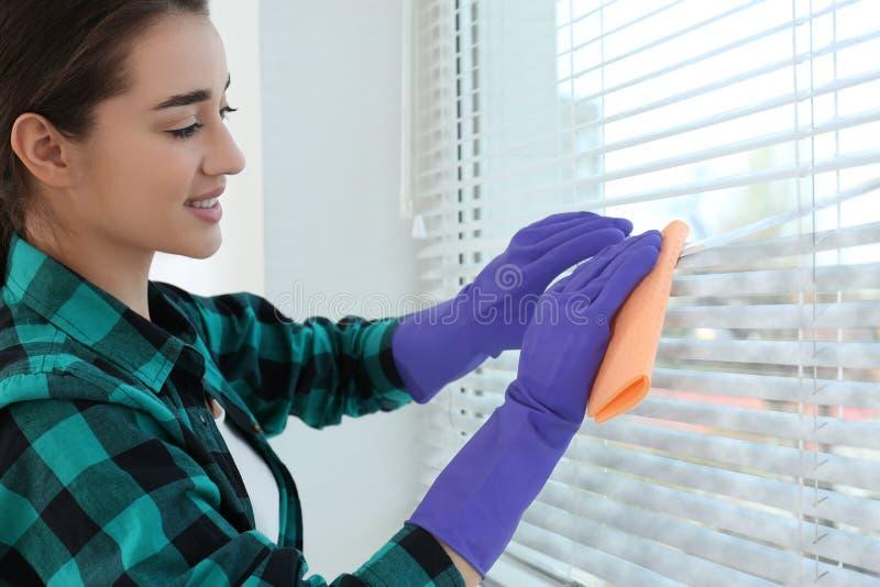 Mujer joven que limpia persianas de ventana con el trapo Antes y despu?s de la limpieza foto de archivo