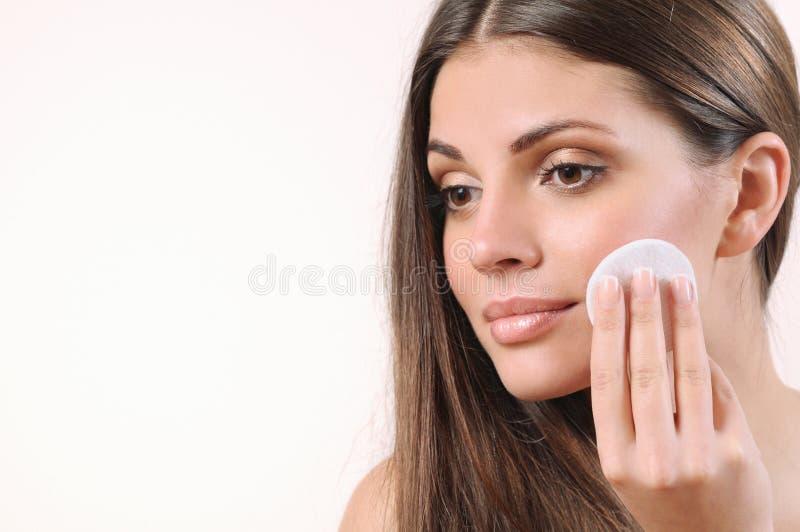 Mujer joven que limpia su piel en el fondo blanco imagen de archivo libre de regalías