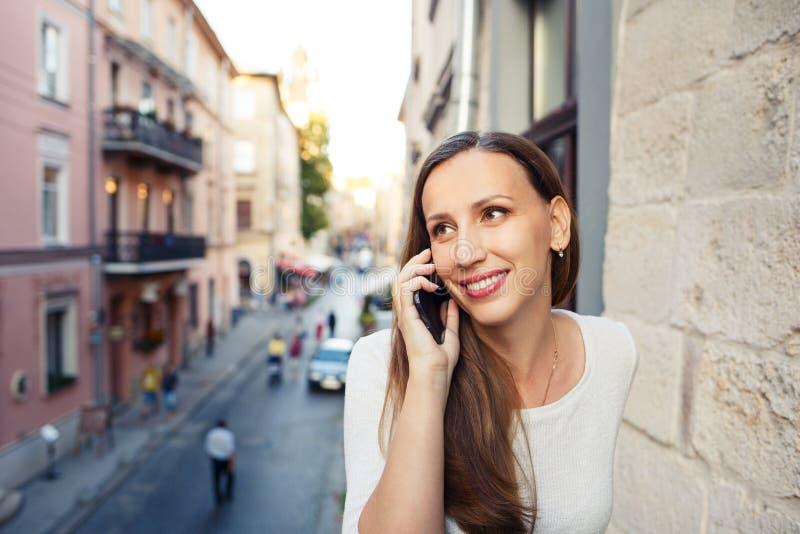Mujer joven que llama el teléfono que se coloca en balcón imágenes de archivo libres de regalías