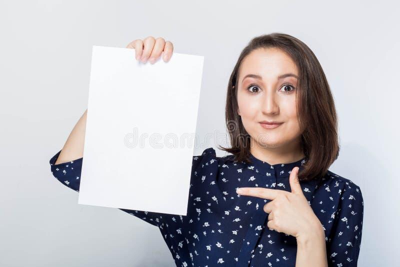 Mujer joven que lleva a cabo al tablero del negocio de la muestra, en blanco sobre el fondo blanco, mirándolo foto de archivo