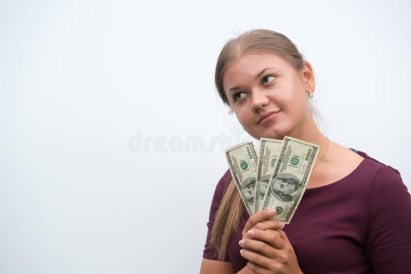 Mujer joven que lleva a cabo dólares disponibles fotografía de archivo libre de regalías