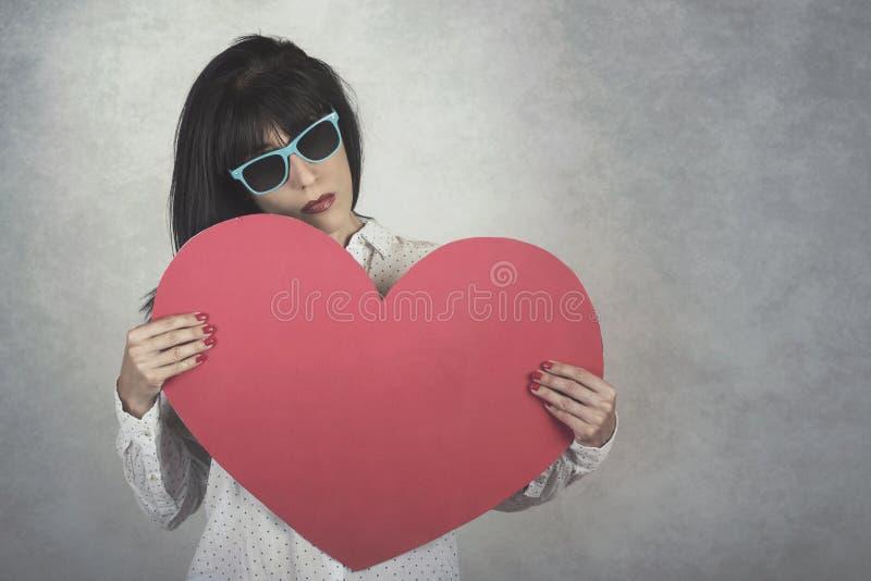 Mujer joven que lleva a cabo el corazón rojo imagenes de archivo