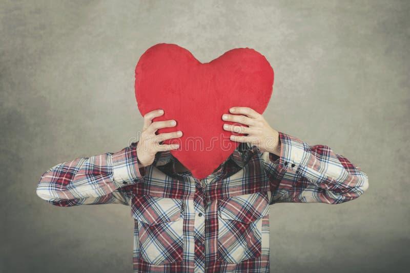 Mujer joven que lleva a cabo el corazón rojo sobre su cabeza fotografía de archivo libre de regalías