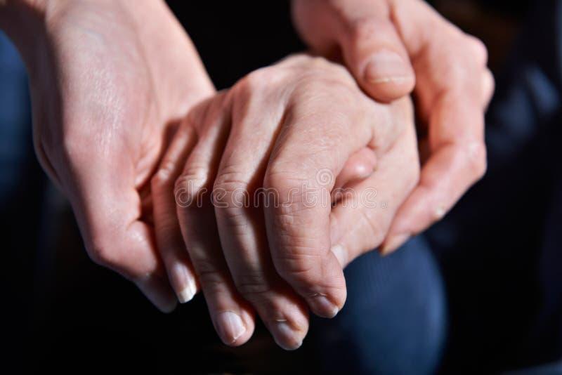 Mujer joven que lleva a cabo la mano de la mujer mayor contra fondo negro fotografía de archivo