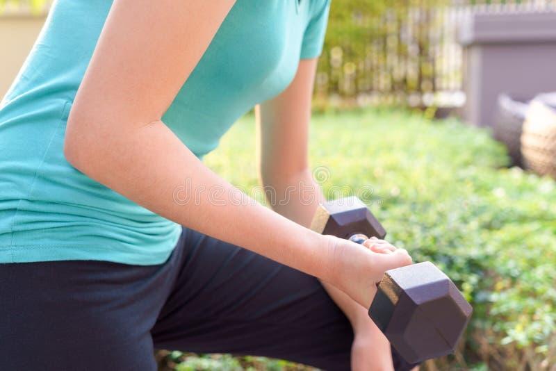 Mujer joven que lleva a cabo la pesa de gimnasia para ejercitar en parque público fotos de archivo libres de regalías
