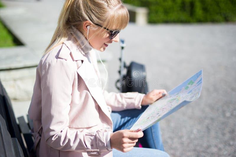 Mujer joven que lleva a cabo la sentada turística del mapa en parque fotografía de archivo