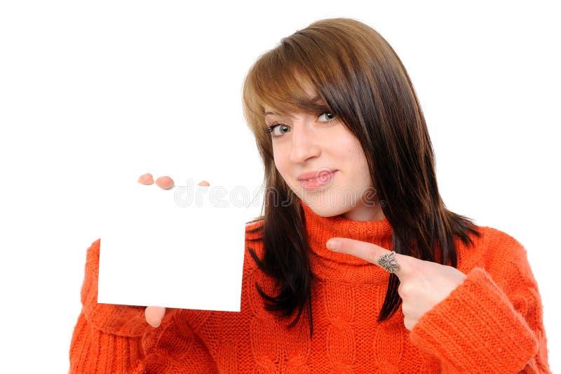 Mujer joven que lleva a cabo a la tarjeta blanca vacía foto de archivo