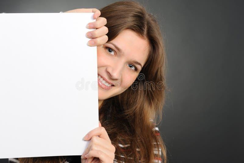 Mujer joven que lleva a cabo a la tarjeta blanca vacía imagen de archivo