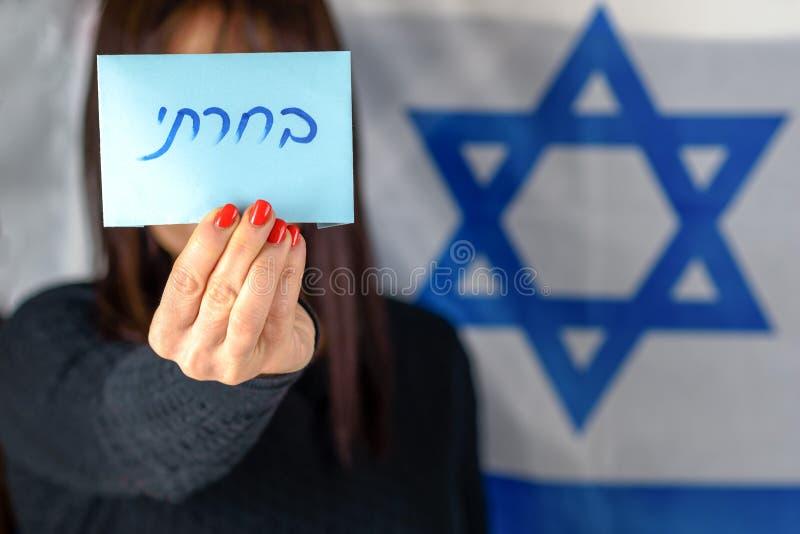 Mujer joven que lleva a cabo la votaci?n Front Of Face en fondo israel? de la bandera Texto hebreo que vot? sobre el papel de vot fotos de archivo libres de regalías