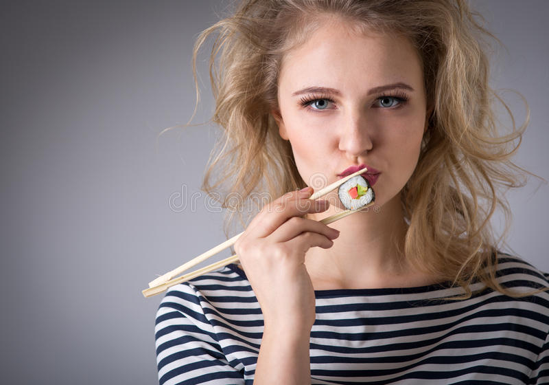 Mujer joven que lleva a cabo los rollos de sushi imagen de archivo