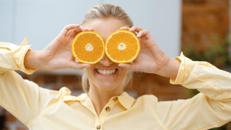 Mujer joven que lleva a cabo rebanadas anaranjadas cerca de sus ojos y sonrisa imagenes de archivo