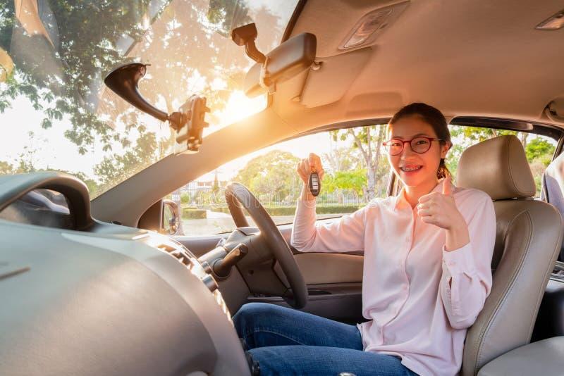 Mujer joven que lleva a cabo una llave de su nuevo coche, concepto del coche de la venta fotografía de archivo libre de regalías