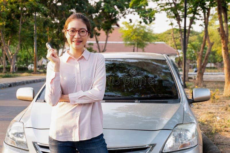 Mujer joven que lleva a cabo una llave de su nuevo coche, concepto del coche de la venta fotos de archivo