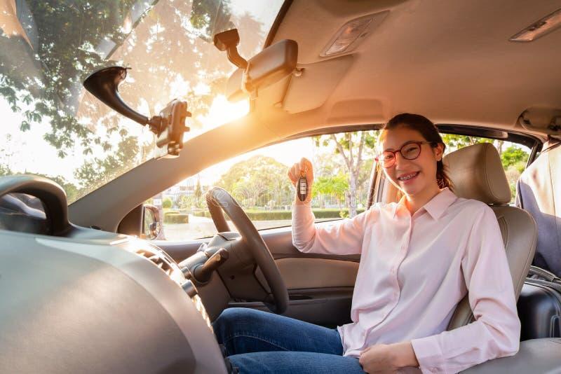 Mujer joven que lleva a cabo una llave de su nuevo coche, concepto del coche de la venta imagen de archivo