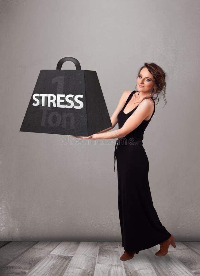 Mujer joven que lleva a cabo una tonelada de peso de la tensión foto de archivo libre de regalías