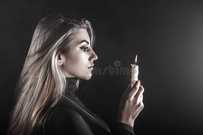 Mujer joven que lleva a cabo una vela en un humo fotografía de archivo