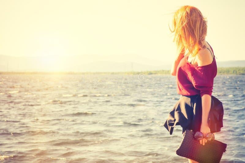 Mujer joven que lleva a cabo viaje al aire libre de la moda de la forma de vida del bolso que camina imágenes de archivo libres de regalías