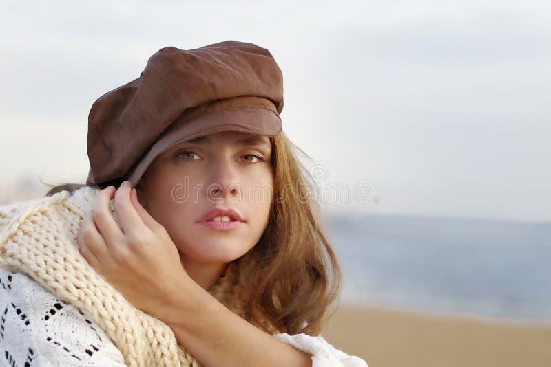 Mujer joven que lleva el quepis marrón fotografía de archivo