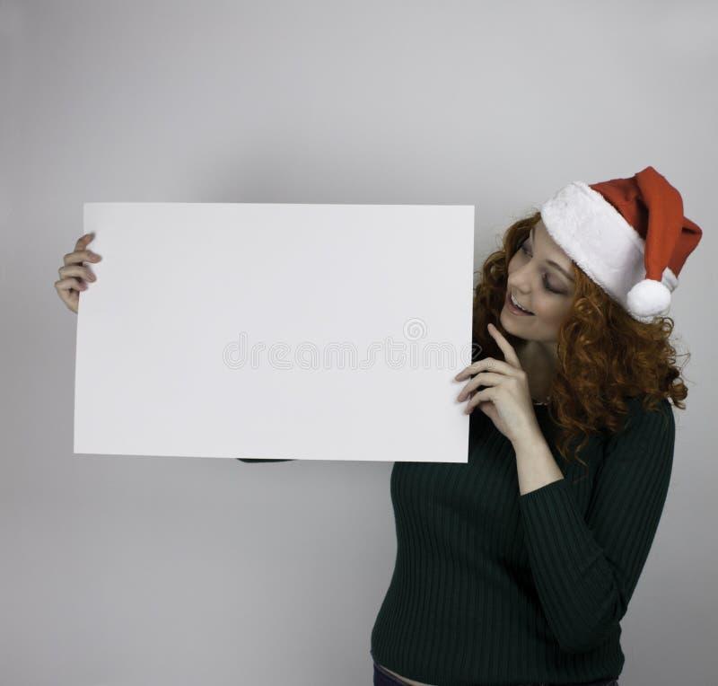 Mujer joven que lleva el sombrero de Papá Noel que lleva a cabo la muestra vacía imagen de archivo libre de regalías