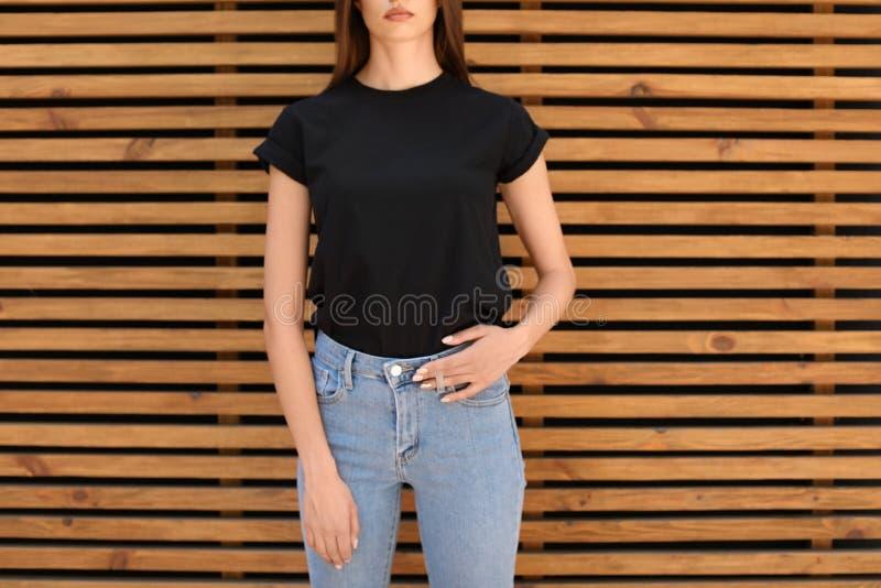 Mujer joven que lleva la camiseta negra contra la pared de madera imagen de archivo libre de regalías