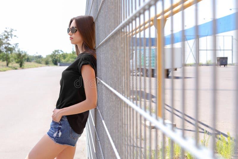 Mujer joven que lleva la camiseta negra en la calle fotografía de archivo