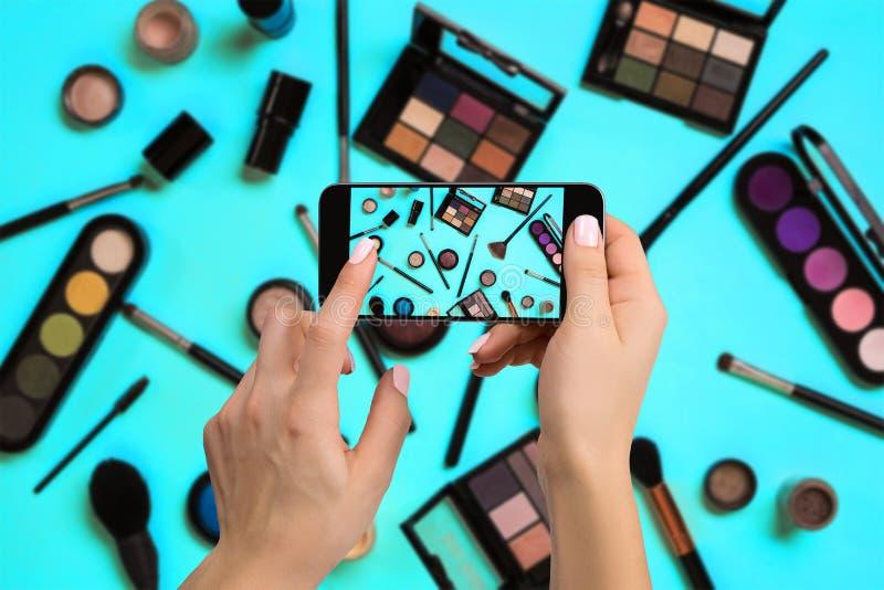 Mujer joven que lleva la foto los cosméticos con el teléfono celular o la cámara digital del smartphone para que posts vendan en  fotos de archivo