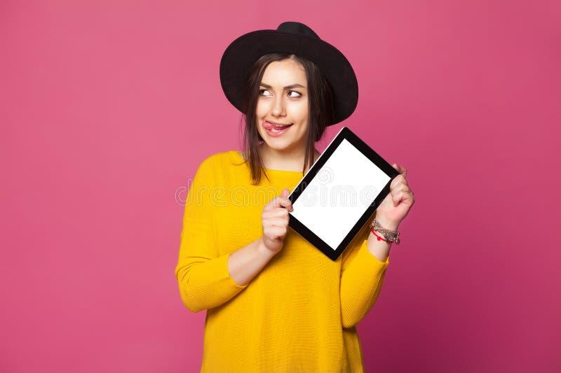 Mujer joven que lleva la ropa casual que sostiene una tableta fotografía de archivo libre de regalías