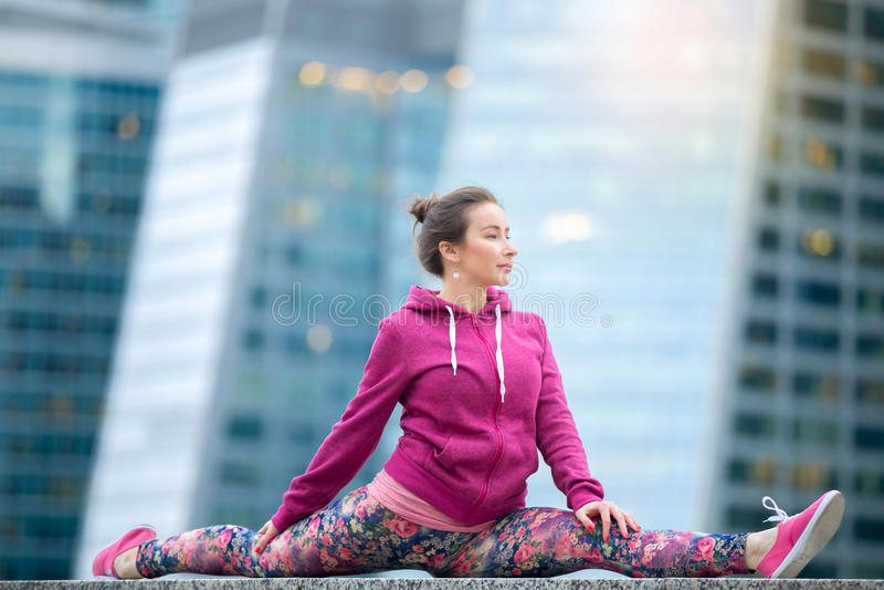 Mujer joven que lleva la ropa de deportes rosada en actitud de dios del mono foto de archivo libre de regalías