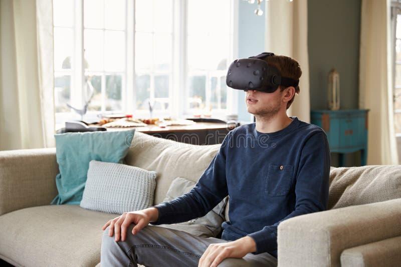 Mujer joven que lleva las auriculares de la realidad virtual en estudio imagenes de archivo