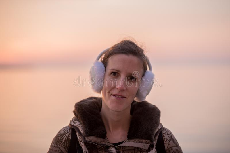 Mujer joven que lleva los calentadores mullidos del oído que miran la cámara fotos de archivo libres de regalías