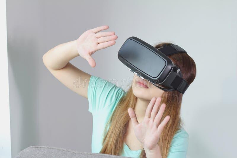 Mujer joven que lleva los vidrios de la realidad virtual en casa imagen de archivo