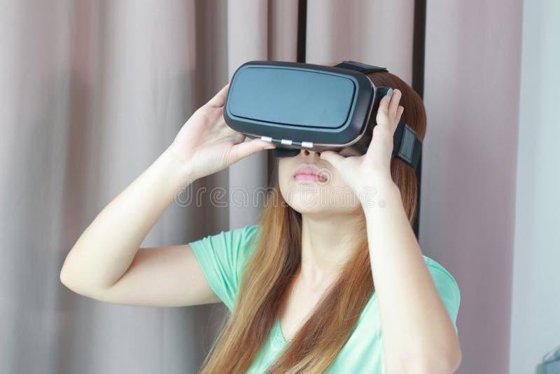 Mujer joven que lleva los vidrios de la realidad virtual en casa fotos de archivo