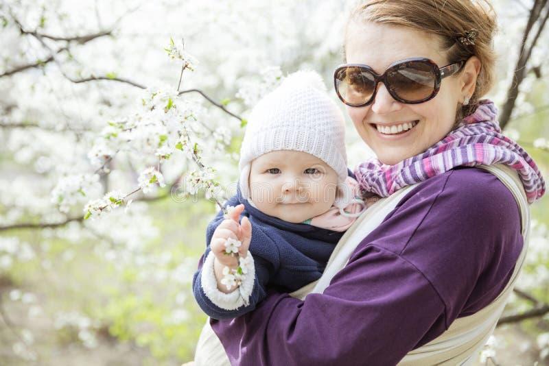 Mujer joven que lleva a su hija del bebé al aire libre en parque de la primavera foto de archivo