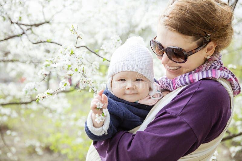 Mujer joven que lleva a su hija del bebé en aire libre tejido del abrigo en parque de la primavera imagenes de archivo