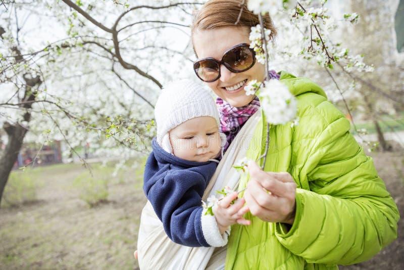 Mujer joven que lleva a su hija del bebé en aire libre tejido del abrigo en parque de la primavera foto de archivo libre de regalías
