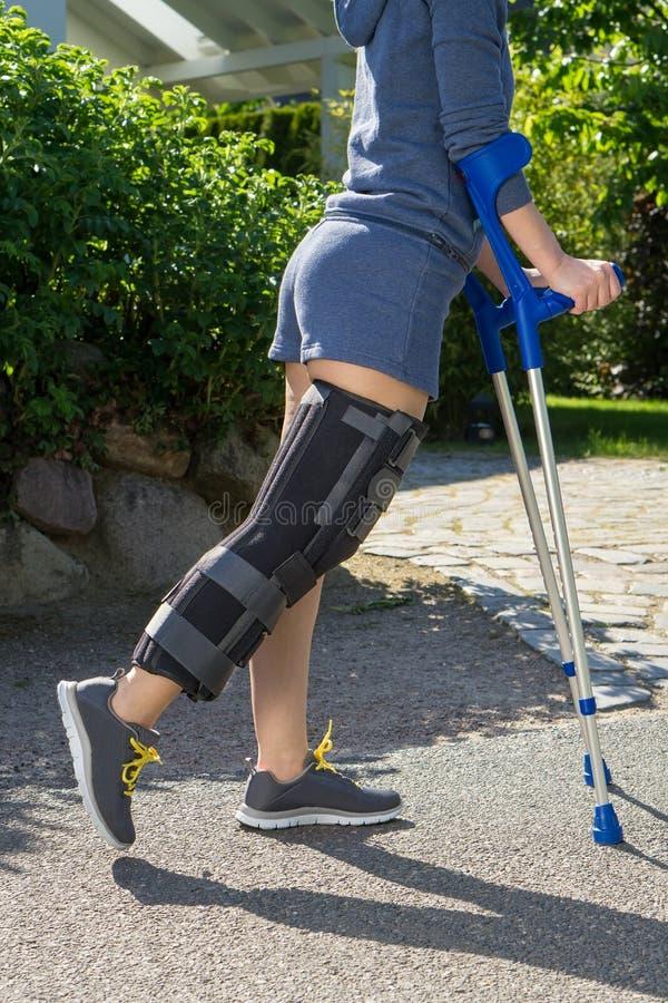 Mujer joven que lleva un apoyo de la pierna, vista lateral fotos de archivo