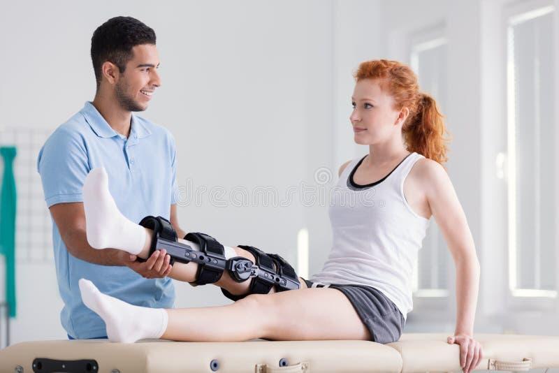 Mujer joven que lleva un apoyo durante la rehabilitación con su fisioterapeuta foto de archivo