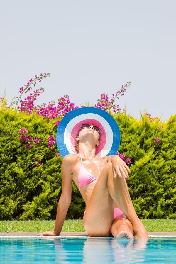Mujer joven que lleva un sombrero de paja imagen de archivo
