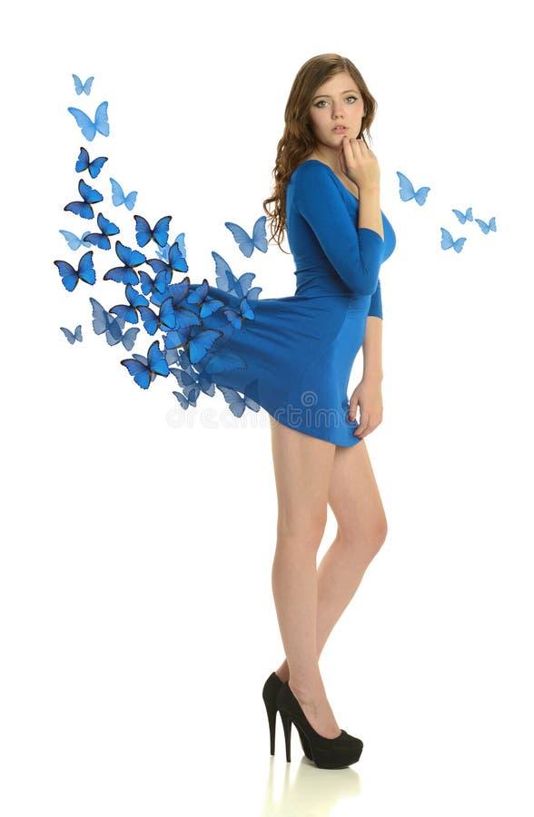 Mujer joven que lleva un vestido azul con las mariposas fotos de archivo libres de regalías