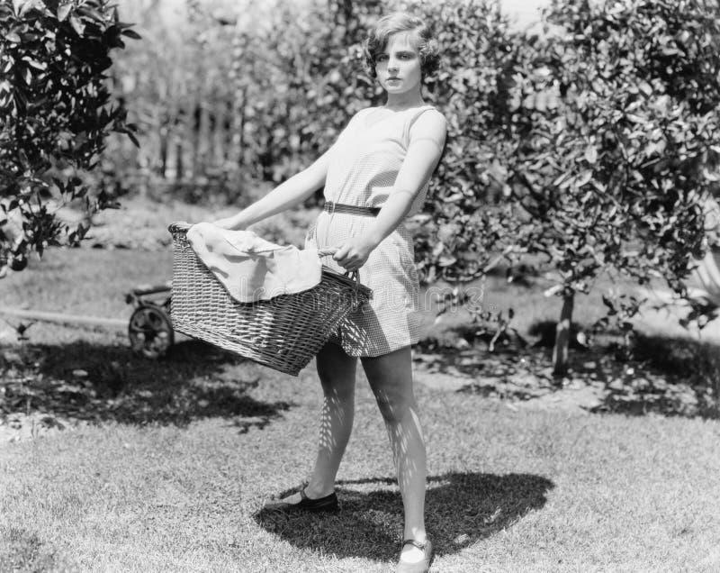 Mujer joven que lleva una cesta de lavadero (todas las personas representadas no son vivas más largo y ningún estado existe Th de fotos de archivo