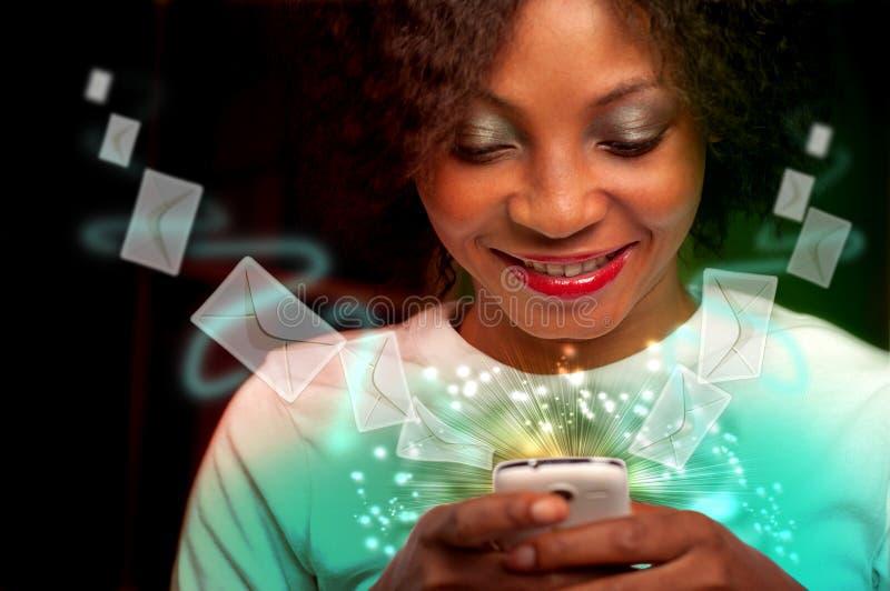 Mujer joven que manda un SMS en el teléfono móvil imagen de archivo