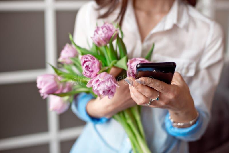 Mujer joven que manda un SMS en su smartphone con una mirada de la concentración como ella se opone a una pared azul foto de archivo