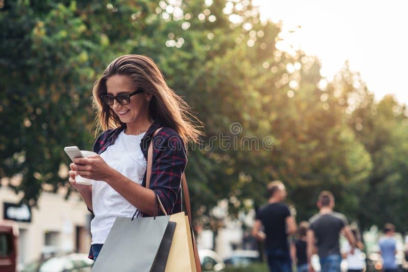 Mujer joven que manda un SMS mientras que disfruta de compras del día foto de archivo libre de regalías