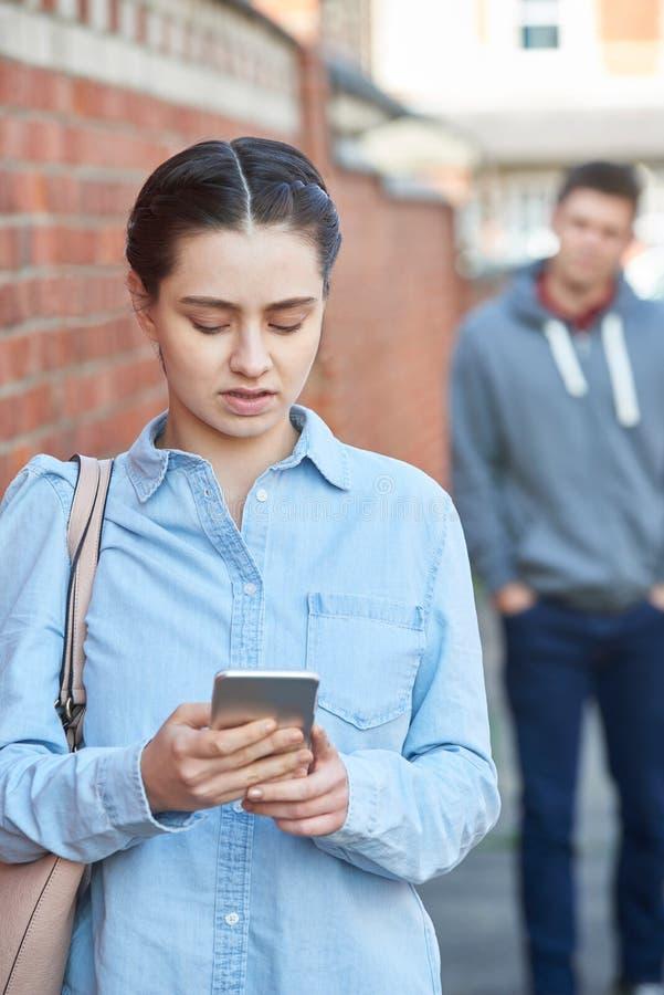 Mujer joven que manda un SMS para la ayuda en el teléfono móvil mientras que siendo Stalke foto de archivo libre de regalías