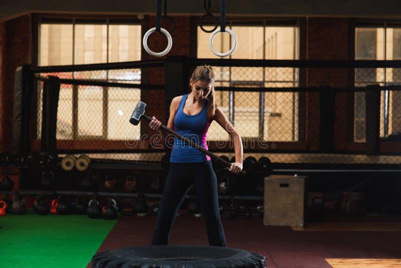 Mujer joven que martilla el neumático grande en el gimnasio imagenes de archivo
