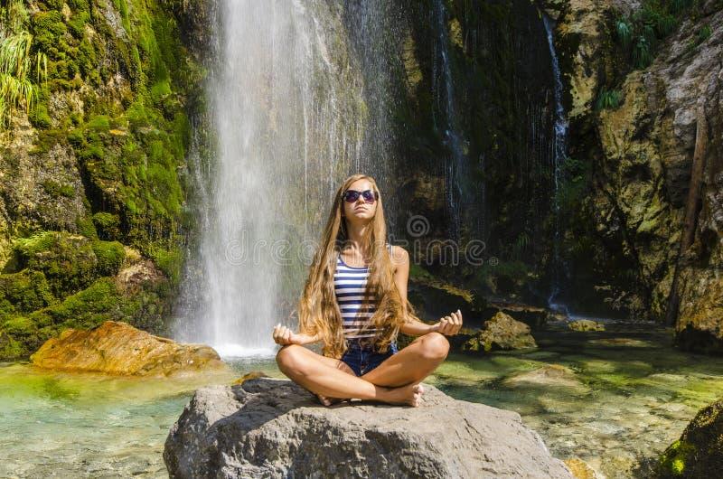 Mujer joven que medita al lado de la cascada hermosa foto de archivo libre de regalías