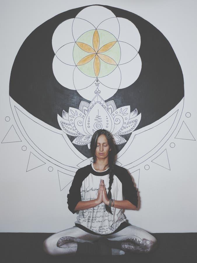 Mujer joven que medita delante de la pintura grande de la mandala en la pared imagenes de archivo