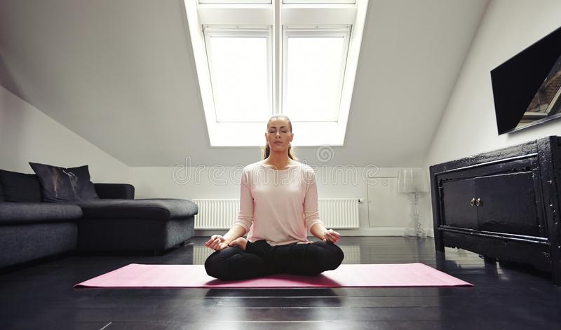 Mujer joven que medita en la posición de loto en casa imagen de archivo