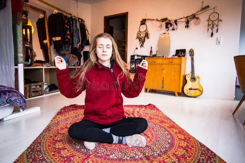 Mujer joven que medita en su apartamento imagen de archivo