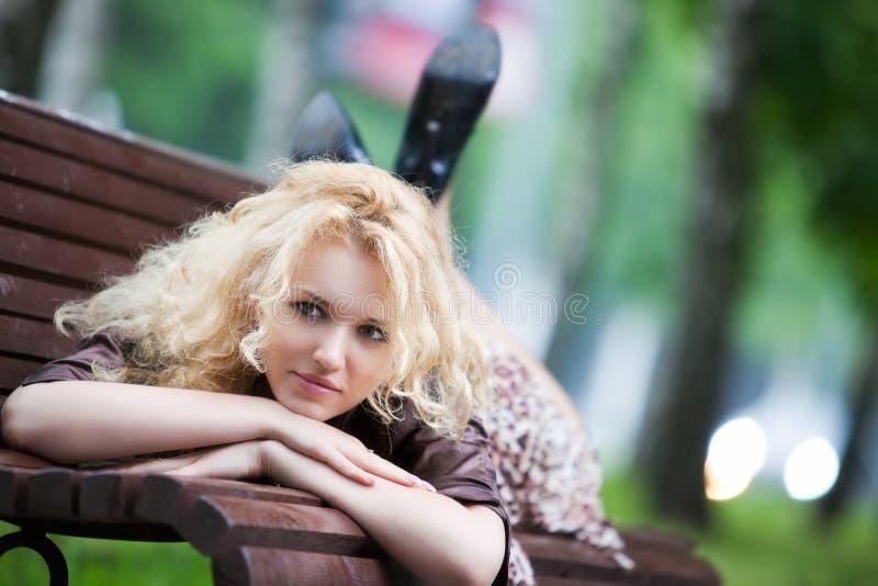 Mujer joven que miente en banco fotografía de archivo libre de regalías